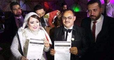 """بالصور.. عروسان يوقعان استمارة """"علشان تبنيها"""" ببورسعيد خلال حفل زفافهما"""