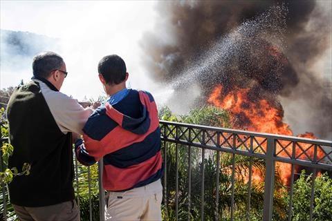 بالصور .. رجال ونساء يستخدمون خراطيم المياه لإخماد حرائق حيفا